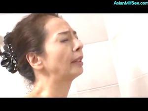 thin cougar woman pushing dildo inside the showr